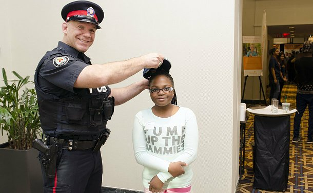 Man in a police uniform putting a police hat on a young girl's head