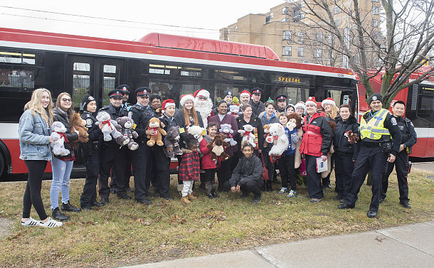 A group of people in front of a TTC bus holding toys