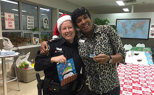 A woman in TPS uniform in a Santa hat with another woman