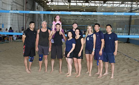 A group of men and women wearing blue shirts on an indoor beach volleyball court