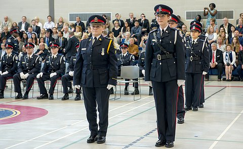 two women in uniform stand facing the chief, one is wearing an inspector uniform the other in constable dress uniform.