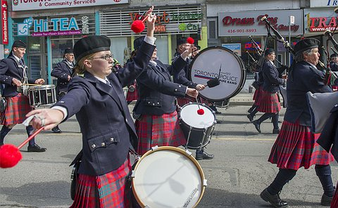 A woman in uniform plays a drum beside another drummer