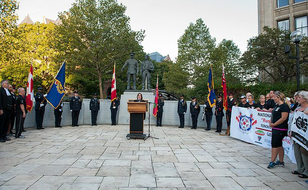 A woman standing at a podium behind her is the ontario police memorial and around her officers stand with flags