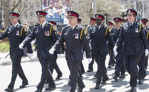 Men and women in TPS uniform marching along a street
