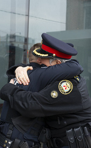 A man and woman in uniform hug