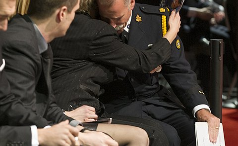 A man in Toronto Police uniform rests his head on a women's shoulder while sitting in the front row of a large audience