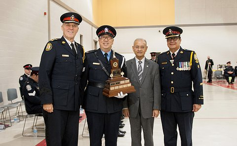 A man with a trophy in his hands, standing alongside the Chief, Chair and Superintendent. All are in uniform except for the Chair.