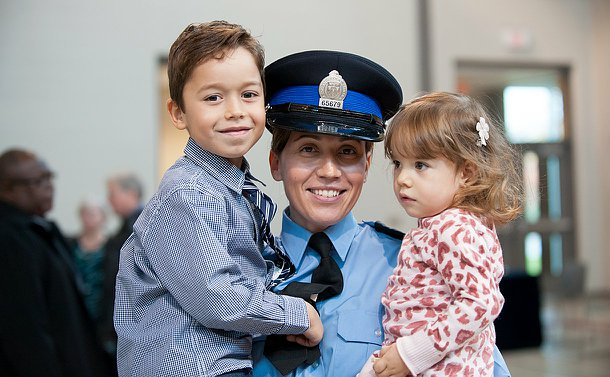 A woman in uniform with her children in her arms smiling.