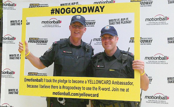 """Two men in TPS uniform holding a large yellow board framing them in the photo with the words #NoGoodWay and """"I took the pledge to become a Yellowcard ambassador"""""""