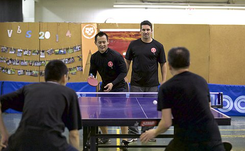 Two pairs of players play table tennis