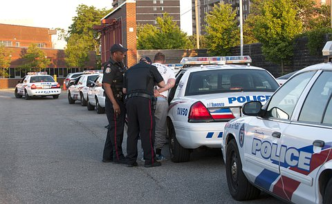 Two men in TPS uniform with another man beside an open back door of a TPS marked vehicle