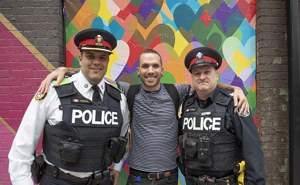 Three men together, two in police uniform