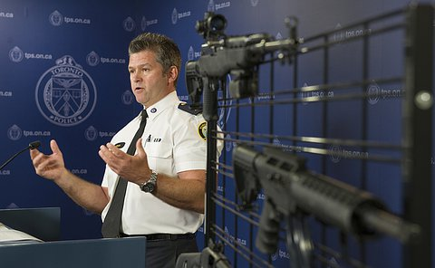 A man at a podium near a metal rack holding several rifles