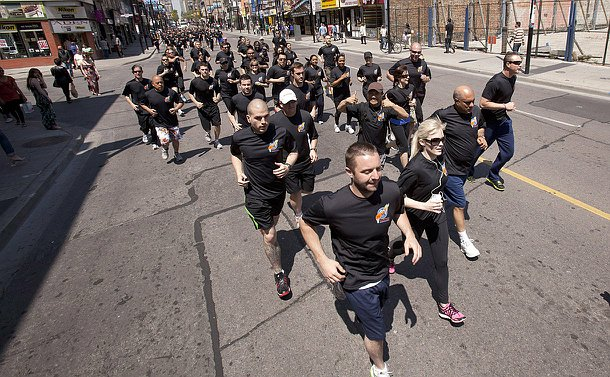Hundreds of people in black T-shirts running down a city street