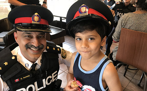 A man in TPS uniform with a boy in a police hat