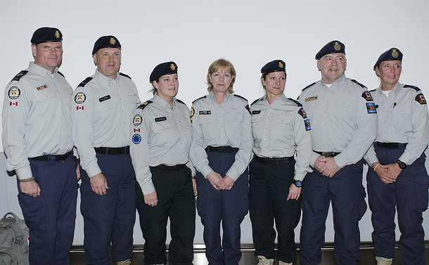 Seven men and women in police uniform stand in a row