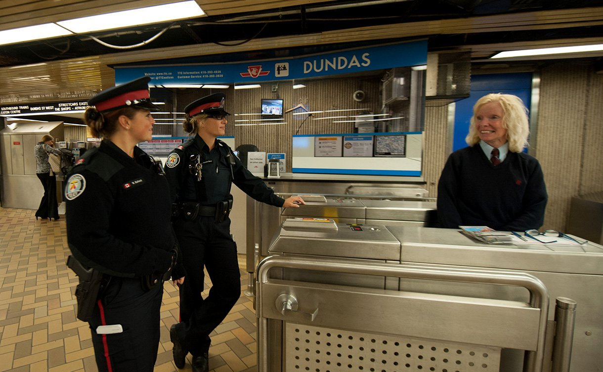 Two officers standing and speaking to a TTC collector who is standing outside the booth.