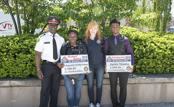 A man in TPS uniform with a woman and a teenage boy and girl holding oversize cheques