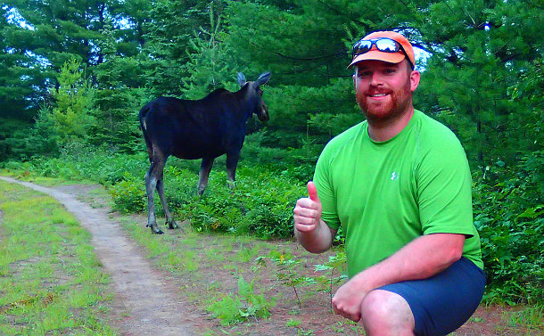 A man with a thumbs up near a moose