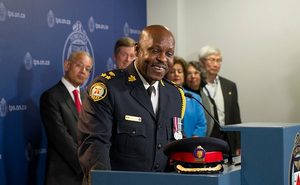 A man in uniform standing at toronto police podium