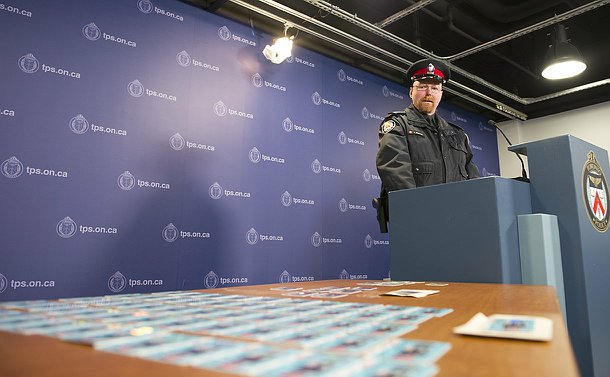 A man in Toronto Police uniform speaks at a podium beside a table full of plastic cards