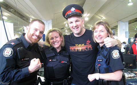 A man and two women in TPS uniform with another man wearing a TPS forge cap