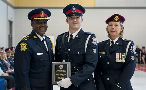 Two men and a woman in TPS uniform. Man in centre holds a plaque