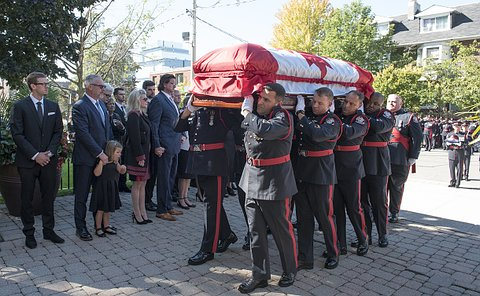 Men in TPS uniform hold a coffin on their shoulders