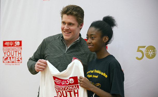 A man with a youth holding a T shirt