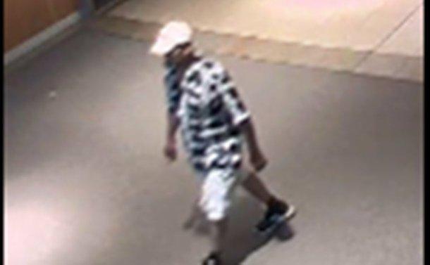 A person wearing a baseball hat, short-sleeved shirt and shorts walking