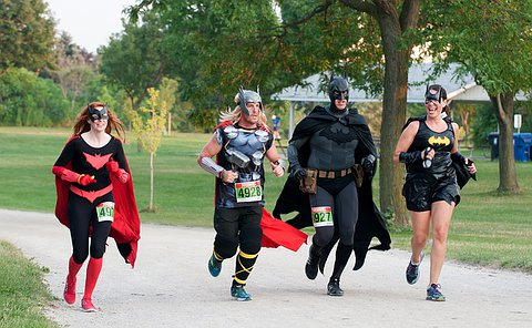 Four people dressed in super hero costumes, batman, bat woman, bat girl and Thor, sprinting in a park.