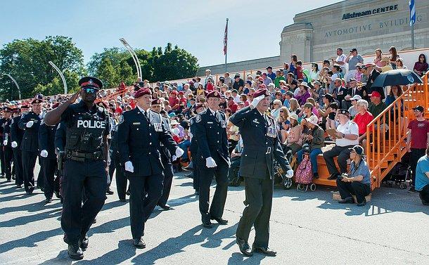 An elderly man saluting facing his right as uniformed members walk behind him
