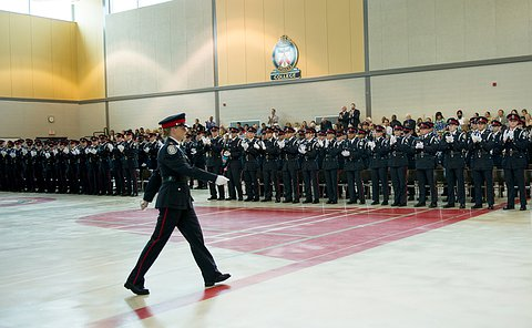 A woman walking in the foreground inside of a gym, with a group of officers in uniforms standing and applauding.