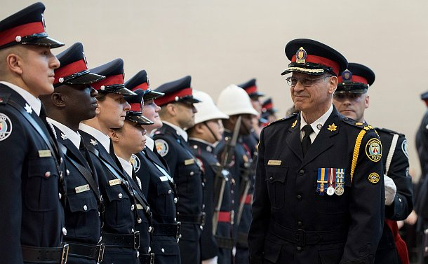 A man in a uniform inspecting officers in uniform