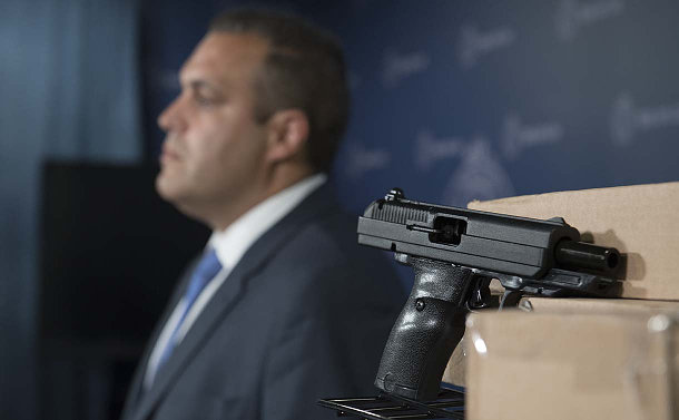 A man out of focus behind a black handgun