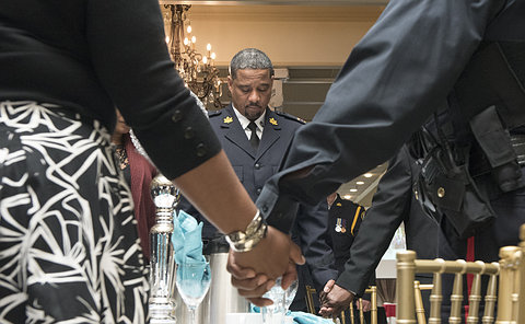 A man in TPS chaplain uniform at a table behind two people holding hands