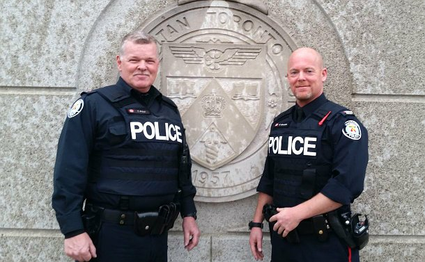 Two men in TPS uniform stand in front of a TPS crest on a wall