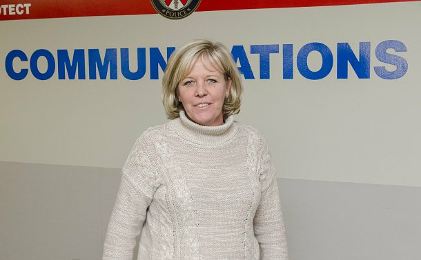 A woman stands in front of a wall with the TPS logo and the word Communications