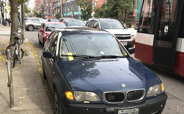 A car parked on a street with a ticket on the windshield