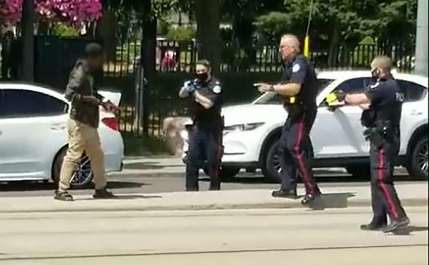 A man holding a knife and three police officers, one holding a gun and another a conducted energy weapon