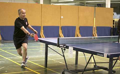 A man hits a table tennis ball standing at side of table