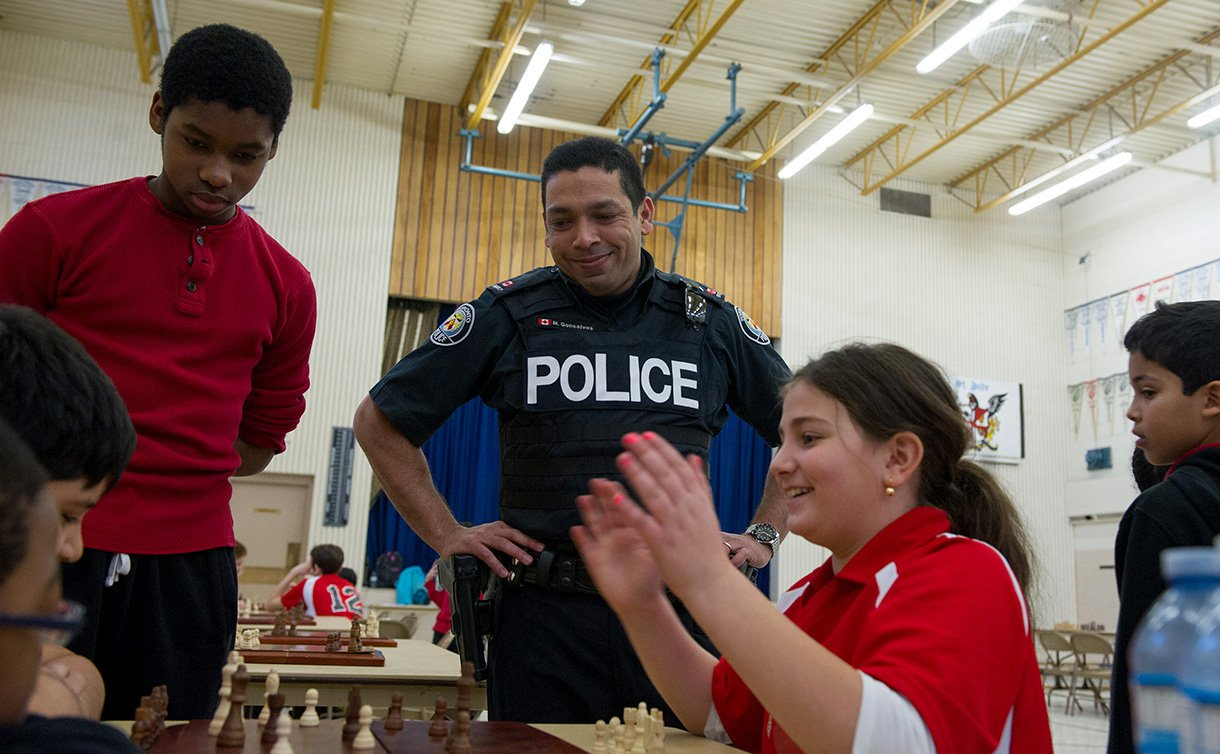 Boys and girls sit near a chess board as one girl claps and a man in TPS uniform stands over them smiling