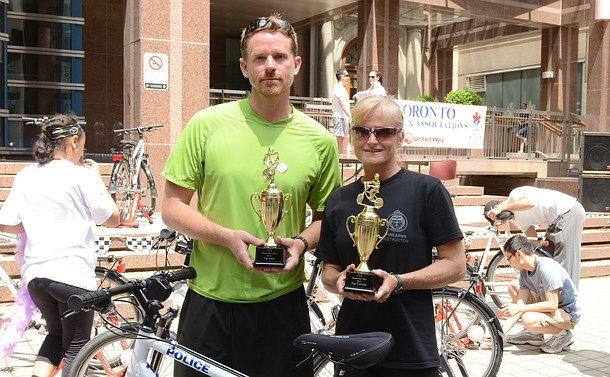 A man and woman holding trophies behind a bicycle
