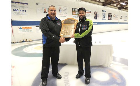 Two men stand on a curling sheet holding a plaque together