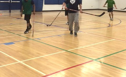 Teenage boys and men holding hockey sticks in a gym