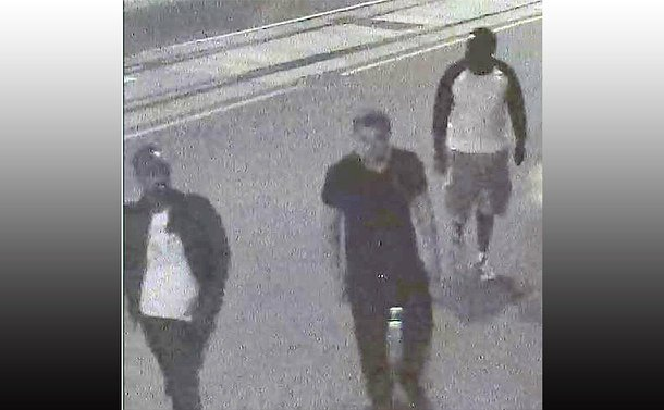 A grainy image of three men crossing a street