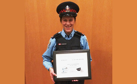 A woman in TPS auxiliary uniform with a certificate