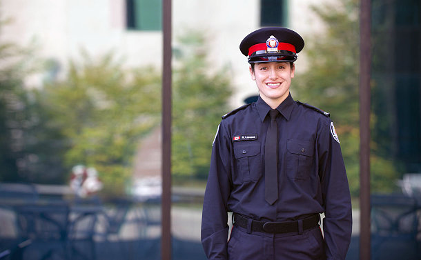 Woman in police uniform stands in front of a glass building