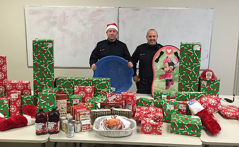 Two men in TPS uniform behind a table full of wrapped gifts and a turkey