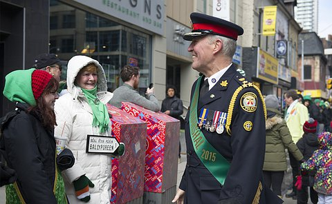 A man in TPS uniform and a green sash smiling at people